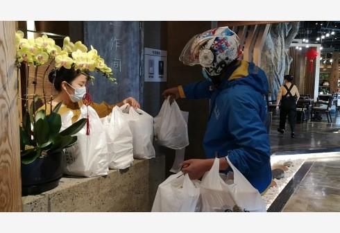2月17日,外賣配送員在成都一家火鍋店交接消費者在線上下單的外賣火鍋(胡旭 攝).jpg